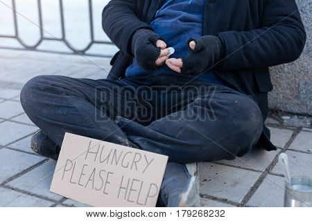 Give me some coins. Untidy man wearing dirty trousers crossing his legs while holding arms bent in elbows