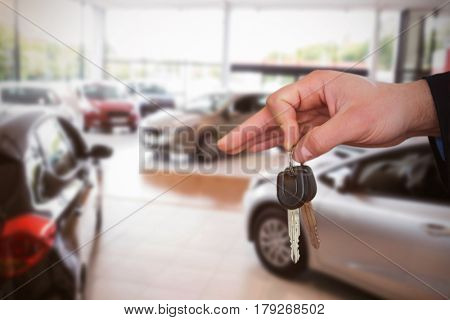 Happy woman receiving car keys against cars parked at showroom