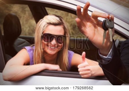 Happy seller holding car keys against happy female driver wearing sunglasses with thumb up