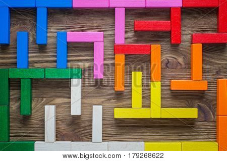 Colorful maze on brown background. The concept of a business strategy analytics search for solutions the search output. Labyrinth of colorful wooden blocks top view flat lay.