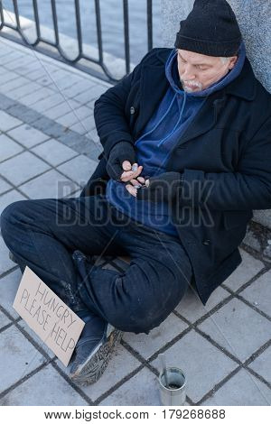 I am busy. Elderly grey-haired man being very attentive while counting coins, leaning on the wall
