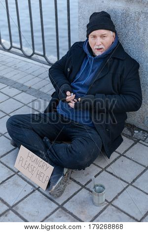 Borrow me some money. Serious bearded man sitting on the pavement keeping legs crossed, leaning on the column