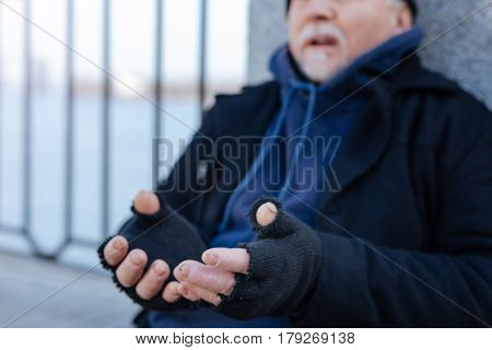 I had family. Homeless pensioner wearing warm clothes stretching hands while leaning on the wall