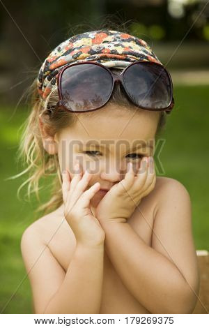 The little girl wears a large adult sunglasses Asian-mestizo