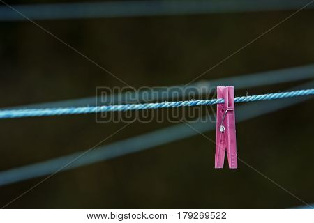 Pink clothes pin isolated on rope , soft background