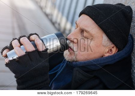 Tea with lemon. Portrait of tired homeless man keeping his eyes closed, holding thermo cup in both hands while drinking