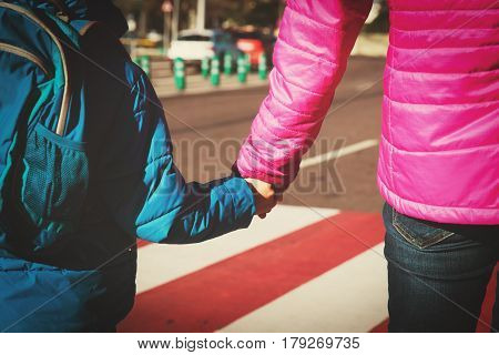 Mother holding hand of little son with backpack at crossroads