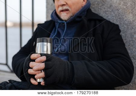 Stay serious. Tired homeless male keeping his mouth opened, holding thermo cup in both hands while crossing fingers
