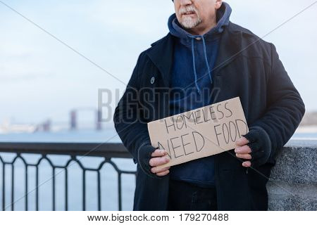 Please read. Gray-haired man standing near bridge railing, showing this poster in this way he asking for some food