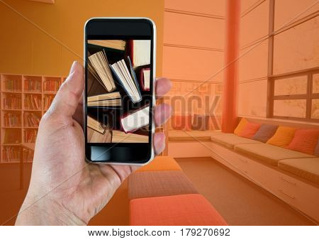 Digital composite of Hand with phone showing standing books against room with orange overlay
