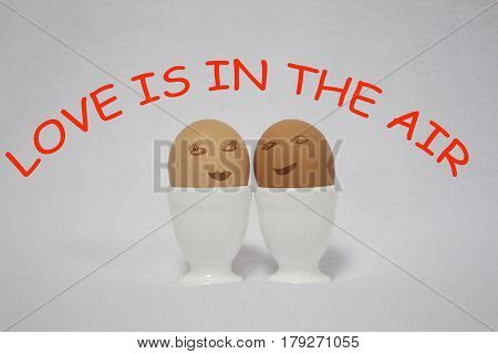 love is in the air. two egs painted like faces of a girl and a guy on the white background.