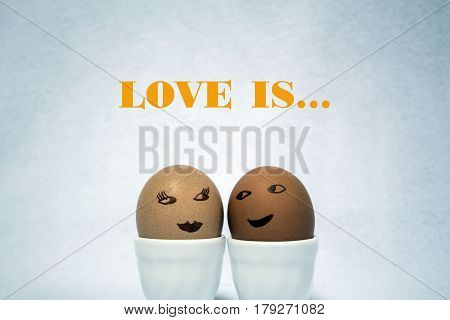 love is... two painted egs like faces of a girl and a guy on the white background.