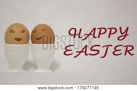 HAPPY EASTER. easter egs.  egs painted like faces of a girl and a guy PASCUA