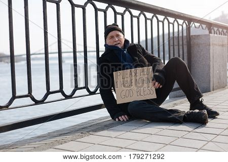 Give me something. Homeless man wearing casual clothes putting right hand on the floor while looking straight at camera
