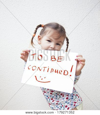 The girl child with a sign in the hands of