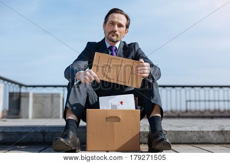 Lets find new job. Serious man sitting outside with box of things holding poster while looking straight on camera