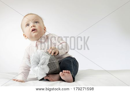 Adorable baby boy with a gift. Postcard for mothers day or any holiday. Cute infant boy sitting with a present and looking up.