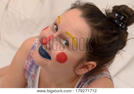 April Fools' joke girl with a clown face grimaces