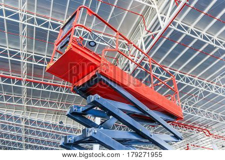 Scissor lift platform with hydraulic system elevated towards a factory roof with construction workers Mobile aerial work platform