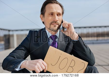 Advise me please. Jobless man wearing costume, keeping telephone in left hand while looking aside