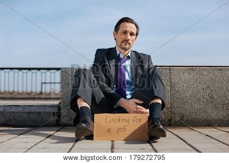 In depression. Young brunette feeling upset looking straight on camera while touching his leg