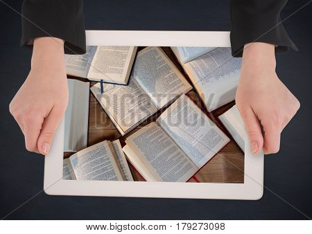 Digital composite of Hands with tablet on navy table showing open books
