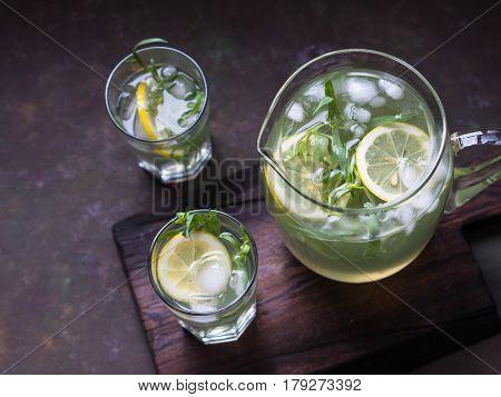 Lemonade tarragon with lemon in a glass jug and glasses