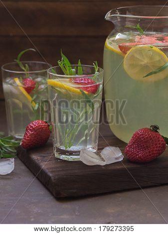 Lemonade tarragon with lemon and strawberries in a glass jar and glasses
