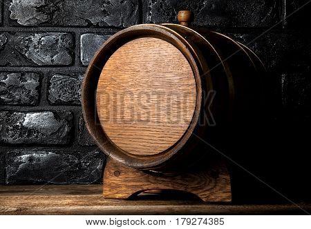 Wooden cask on table near black brick wall
