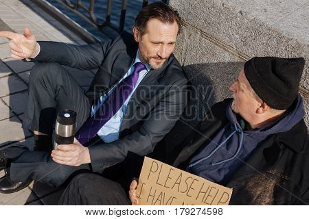 Interesting conversation. Disappointed office worker keeping thermos with hot tea sitting on the pavement while looking at his interlocutor