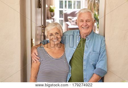 Happy portrait of a content senior man with his arm around his wife's shoulder while standing together at the front door of their home