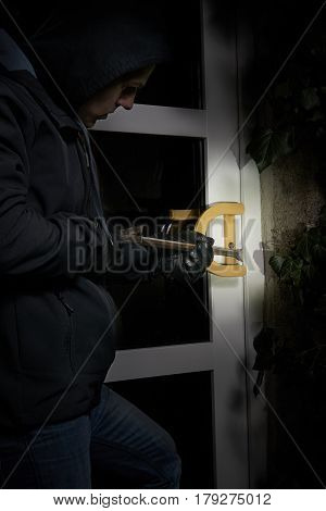 burglar trying to get into a house using a crowbar with torchlight flare