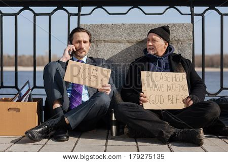 Yes boss. Homeless person holding cardboard in hands crossing legs sitting on the pavement while looking at his friend