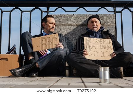 Let me think. Poor homeless man holding cardboard in hands crossing legs while sitting on the pavement