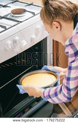 Girl Taking Cheesecake Out Of Oven In Kitchen