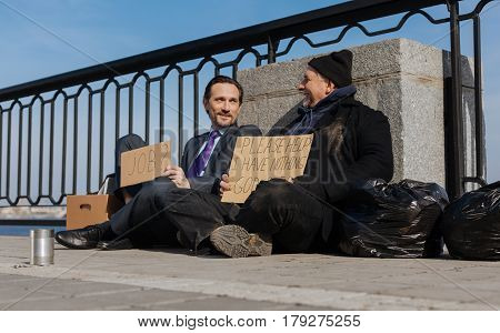 For new life. Two men looking at each other, homeless sitting near garbage bag keeping smile on face
