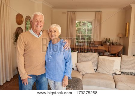 Portrait of a smiling senior man with his arm around his wife's shoulder standing together in their living room at home