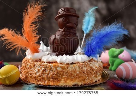 a mona de pascua, a cake eaten in Spain on Easter Monday, topped with a chocolate chick, on a rustic wooden surface full of decorated eggs and feathers of different colors