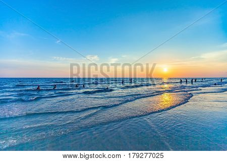 beautiful sunset at the sea with people silhouette on the beach and colorful shading of sunlight and sky