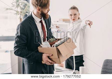 Young Upset Fired Businessman With Cardboard Box And Boss In Office