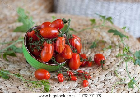Cherry tomatoes on their branches in a bowl. Rattan background, right copy space.