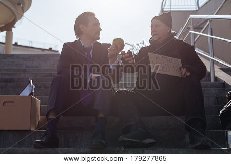 Understand you. Two males sitting on the stairs looking at each other while having conversation