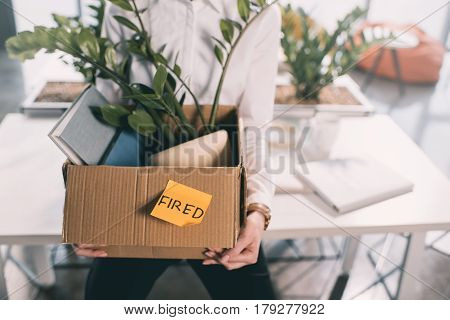 Cropped shot of young fired businesswoman holding box with belongings