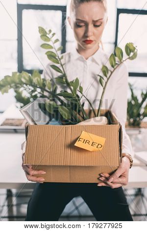 Young depressed fired businesswoman holding box with belongings