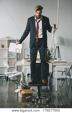 Young Fired Businessman Standing On Chair And Trying To Hang Himself In Office