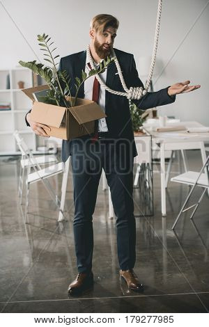 Young Upset Businessman Holding Box With Belongings And Trying To Hang Himself