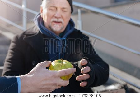 Just take it. Male hand holding big green fruit giving it to poor homeless person that is sitting outdoors