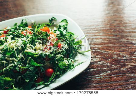 Fresh salad with tomato ruccola on the kitchen table.