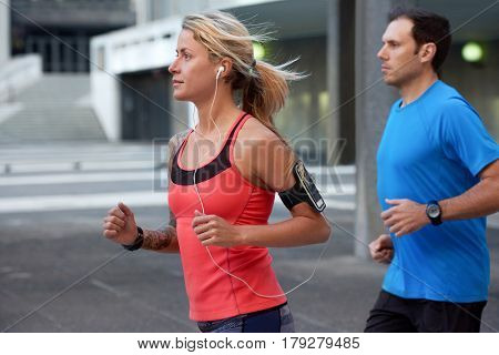 Exercising woman listening to her running playlist on earphones wearable device smartphone