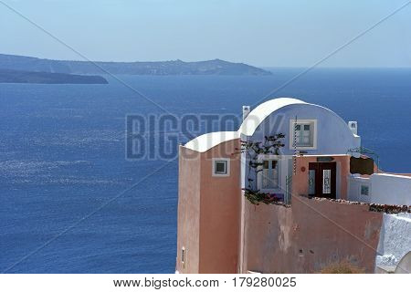 House in traditional Cycladic architectural style, on the edge of the volcano caldera of Santorini island, Greece.